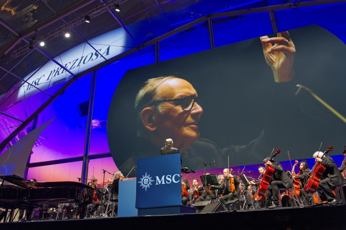 With Preziosa lit in the background, composer Ennio Morricone conducts the Roma Sinfonietta Orchestra